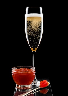 Elegant glass of yellow champagne with red caviar on golden spoon