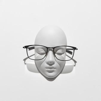 Элегантные очки на гипсовой скульптуре лица с тенями на белой стене, копией пространства. очки для чтения и людей с нарушением зрения. вид сверху.