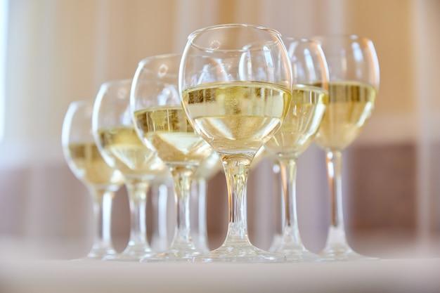 Элегантные бокалы с шампанским, стоящие в ряд на сервировочном столе во время вечеринки или торжества