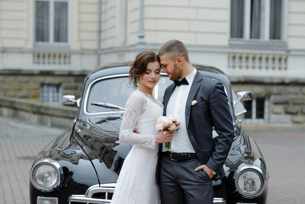 エレガントなゴージャスな花嫁とハンサムな新郎が光の中でスタイリッシュな黒い車を受け入れます。