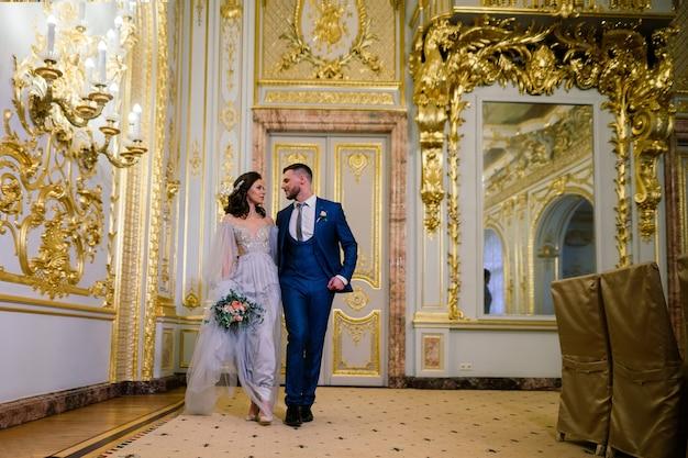 놀랍고 오래된 부유한 방에서 우아한 화려한 신부와 세련된 신랑. 럭셔리 웨딩 컨셉