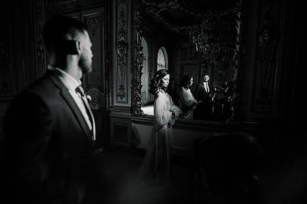 놀랍고 오래된 부유한 방에서 우아한 화려한 신부와 세련된 신랑. 복고 스타일의 특이한 웨딩 커플, 럭셔리 웨딩 컨셉