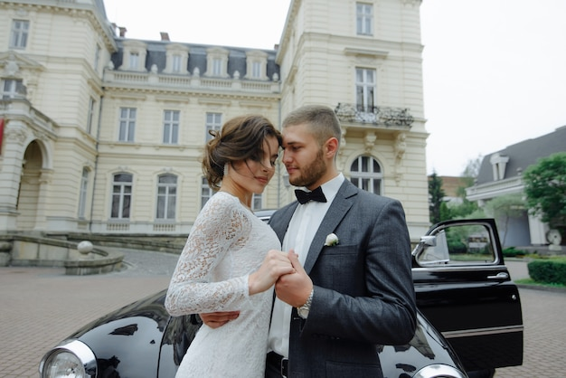 Elegant gorgeous bride and handsome groom embracing in stylish black car in light.