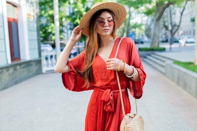 屋外を歩くサンゴのロングドレスでエレガントな豪華な女性。明るい夏の色。おしゃれなストリートルック。