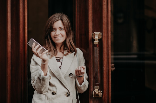 Elegant gorgeous lady in raincoat, holds mobile phone, waits for call