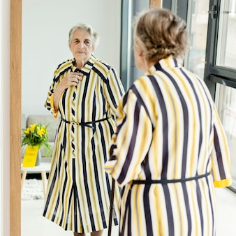 Elegant grandmother looking at herself in the mirror