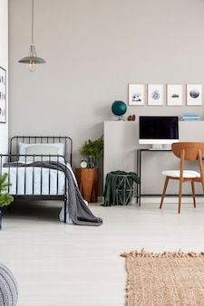 Elegant grey teenager bedroom with single metal bed with blue bedding and grey blanket real photo