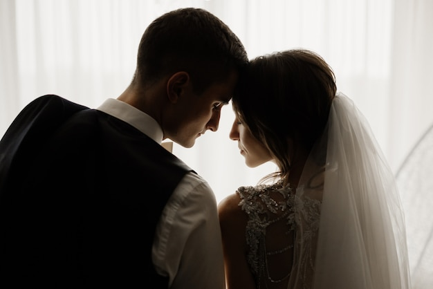 Элегантный жених и красивая невеста стоят перед окном, склонив головы друг к другу. свадьба, любовь, концепция отношений. низкий ключ. портрет в полный рост.