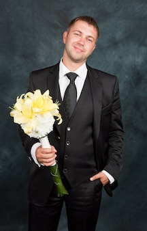 Elegant groom is holding bouquet of yellow lilies in a studio
