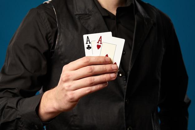 우아한 남자, 포커 초보자, 검은 조끼와 셔츠. 포즈를 취하는 동안 두 장의 카드, 에이스를 들고
