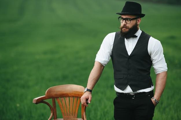 Элегантный парень рядом с деревянным стулом