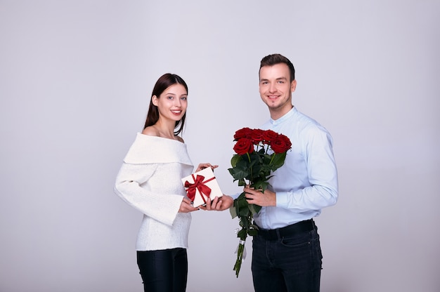 Elegant guy smiles, giving his beautiful womanfriend roses and a gift.