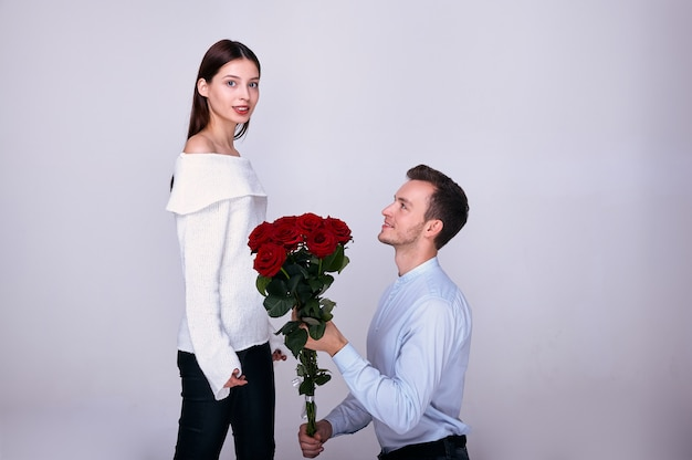 An elegant guy stands on one knee and gives his womanfriend red roses.