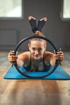 Элегантный учитель гимнастики перевернутыми руками поддерживает тело на полу, а ноги на кольце для пилатеса с растянутым телом развивают мягкость в студии на серой стене.