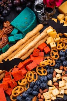 Элегантные закуски на хэллоуин. сырная тарелка с ягодами, виноградом, орехами и закусками