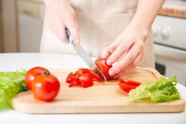 若い女の子の優雅な手は、木製のまな板の上でジューシーな赤いトマトを半分に切りました。材料と野菜の準備。ダイエット、栄養、健康的なライフスタイルのためのオーガニック製品。