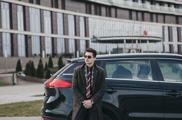 コートを着たエレガントなハンサムな男が新しい車の隣に立っています。自動車保険