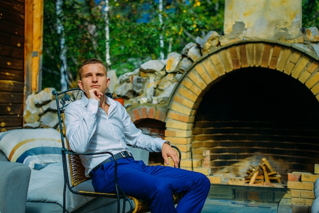 Elegant handsome young man sitting by the fireplace in a vintage outdoor veranda