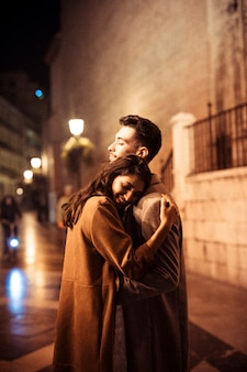 Elegant happy woman hugging with young man on promenade at night