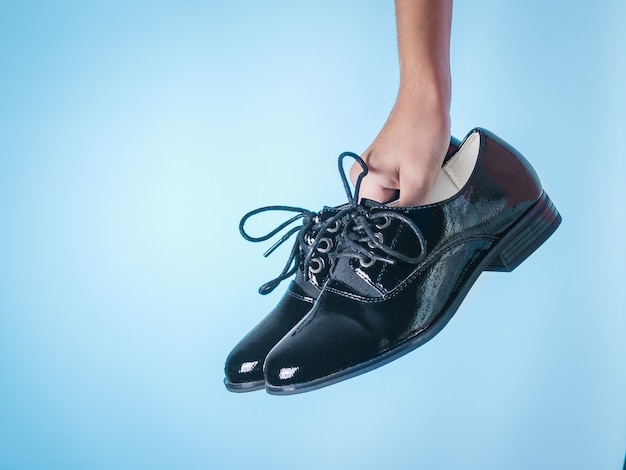 Elegant high heels with laces in the hands on a blue surface