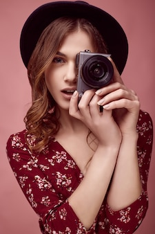Elegant hipster girl in red dress, black hat and glasses with camera