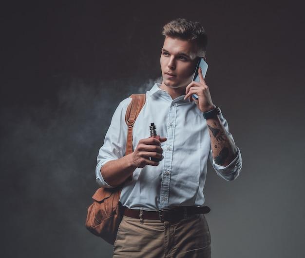 어두운 배경에서 격리된 공식적인 맞춤 옷을 입은 우아한 힙스터 남자. 전화 통화 하는 배낭 세련 된 관광입니다.