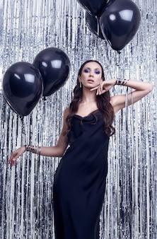 Elegant hispanic brunette woman in luxurious black dress holds balloons