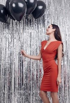 Elegant hispanic brunette woman in luxurious red dress holds balloons