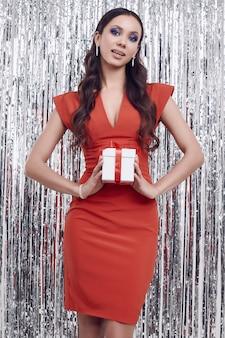 Elegant hispanic brunette woman in luxurious red dress holds a gift box