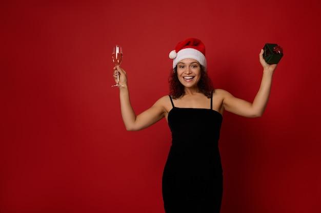 샴페인 플루트와 스파클링 와인과 선물 상자를 들고 산타 모자를 쓴 우아한 히스패닉 여성은 복사 공간이 있는 빨간색 배경 위에 포즈를 취한 이빨 미소를 짓고 있습니다. 메리 크리스마스 그리고 새해복 많이 받으세요