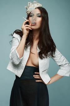 Elegant hot brunette woman in gold crown smoking a cigarette