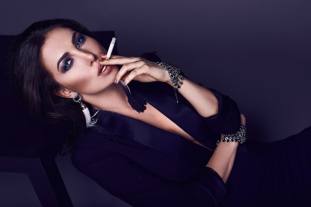 Elegant hot brunette woman smoking a cigarette