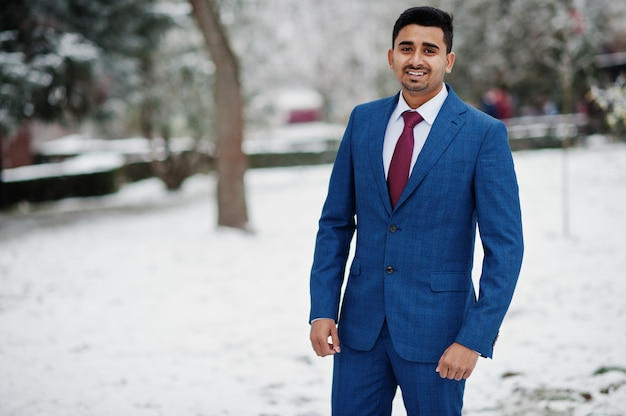 Elegant indian fashionable man model on suit posed at winter day.
