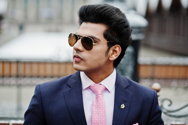 Elegant indian macho man model on suit and pink tie, sunglasses posed on winter day and sitting on bench.