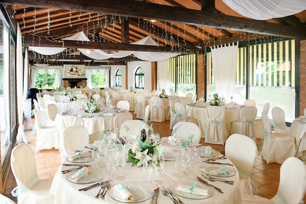 Elegant interior design of restaurant with round tables with tableware and flowers in delicate white and blue tones served for festive wedding reception