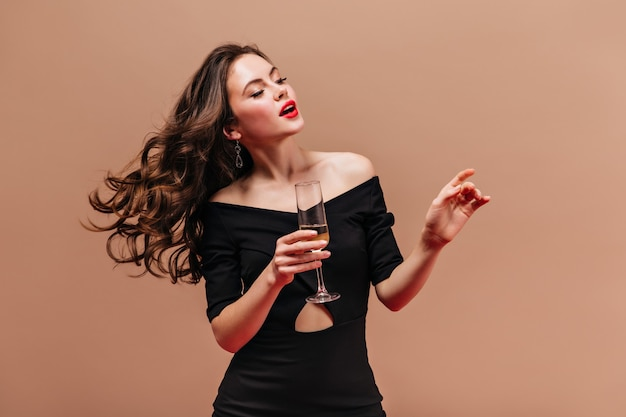 Elegante signora in abito nero con in mano un bicchiere di spumante su sfondo beige.