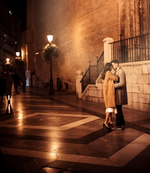 Elegant lady hugging and kissing with young guy on street