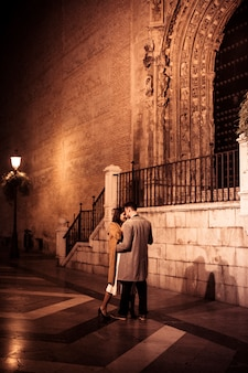 Elegant lady hugging with young guy on street in evening