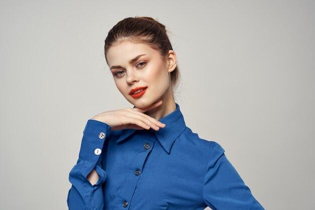 彼女の手で身振りで示す青いシャツのエレガントな女性