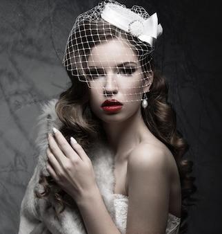 ベールとネイルデザインの毛皮のコートでエレガントな女性。冬の画像。灰色の背景でスタジオで撮影された写真。美顔。