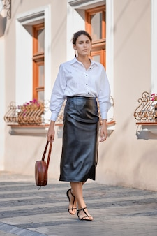 Elegant lady in leather skirt and white shirt walking down the street with leather hand bag