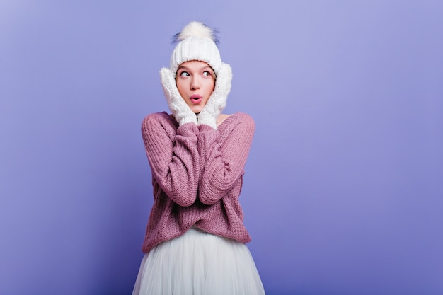 Elegant lady in mittens and hat expressing amazement. shocked young woman in trendy hat posing with surprised face.