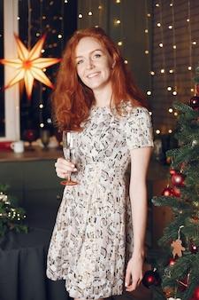 クリスマスツリーの近くのエレガントな女性。シャンパンで家にいる女性。