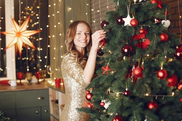 크리스마스 트리 근처 우아한 아가씨입니다. 집에서 여자