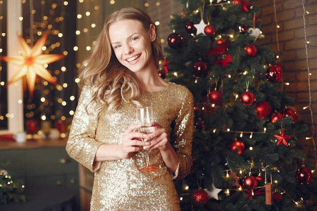 Elegant lady near christmas tree. woman at home with champagne.