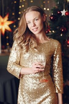 Signora elegante vicino all'albero di natale. donna a casa con champagne.