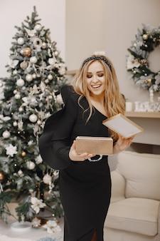クリスマスツリーの近くのエレガントな女性。部屋の女性。エレガントな黒のドレスを着た女性。