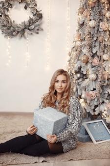 クリスマスツリーの近くのエレガントな女性。部屋の女性。銀のドレスを着た女性。