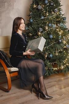 크리스마스 트리 근처 우아한 아가씨입니다. 방에있는 여자.