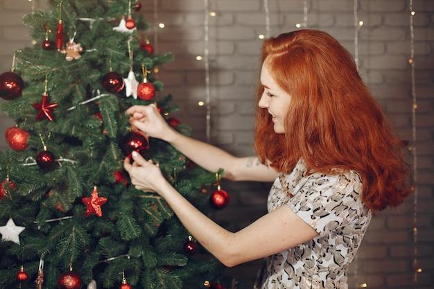 クリスマスツリーの近くのエレガントな女性。